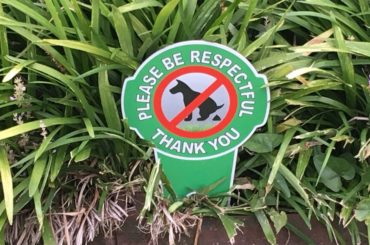 Front yard sign urging folks to pick up their dog's pet waste.