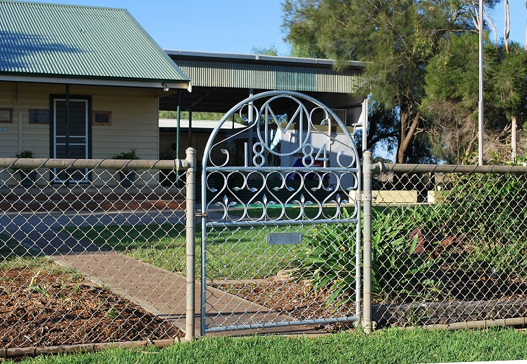 Chain link fence with gate in front of house