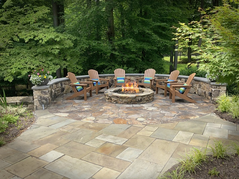 lawn chairs arranged around a fire pit on a round stone patio