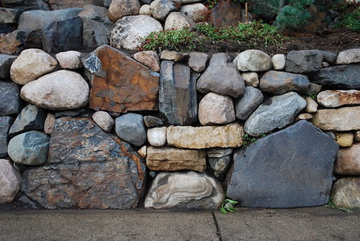 Close up of a retaining wall with different shaped and different colored rocks