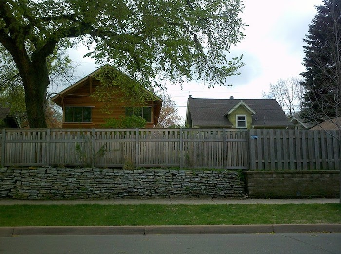 A yard fence stands above a retaining wall