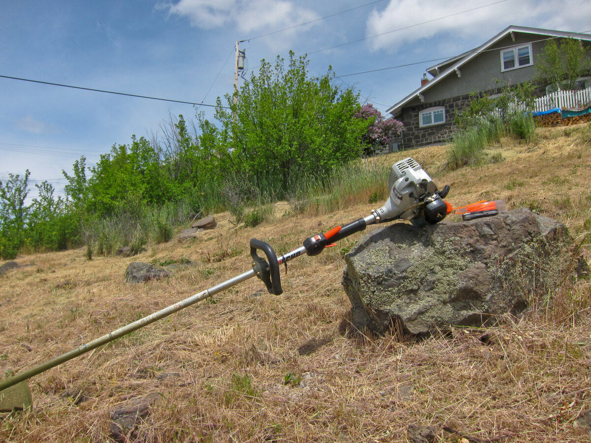 Gas string trimmer laying on a rock in a field