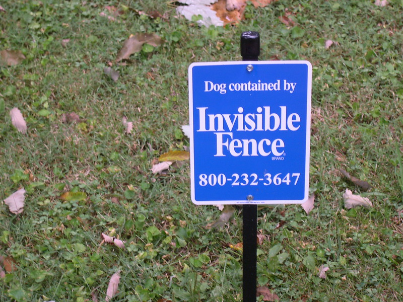 """Sign saying """"Dog Contained by Invisible Fence Brand"""""""