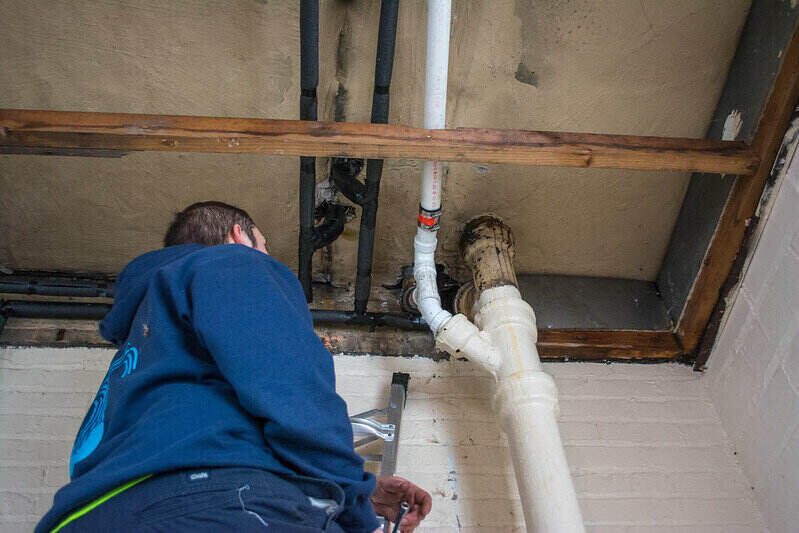 Worker fixing a pipe in the upper part of a ceiling