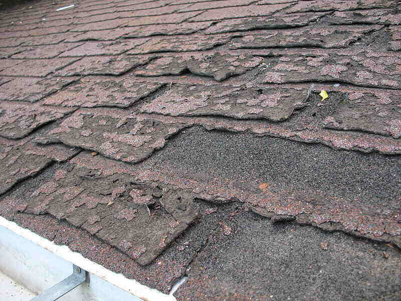 Close-up of old asphalt shingles that are in need of replacement