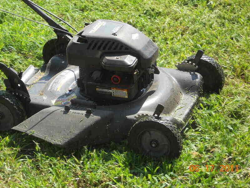 Close-up of a mulching lawn mower with grass clippings all over the top of it