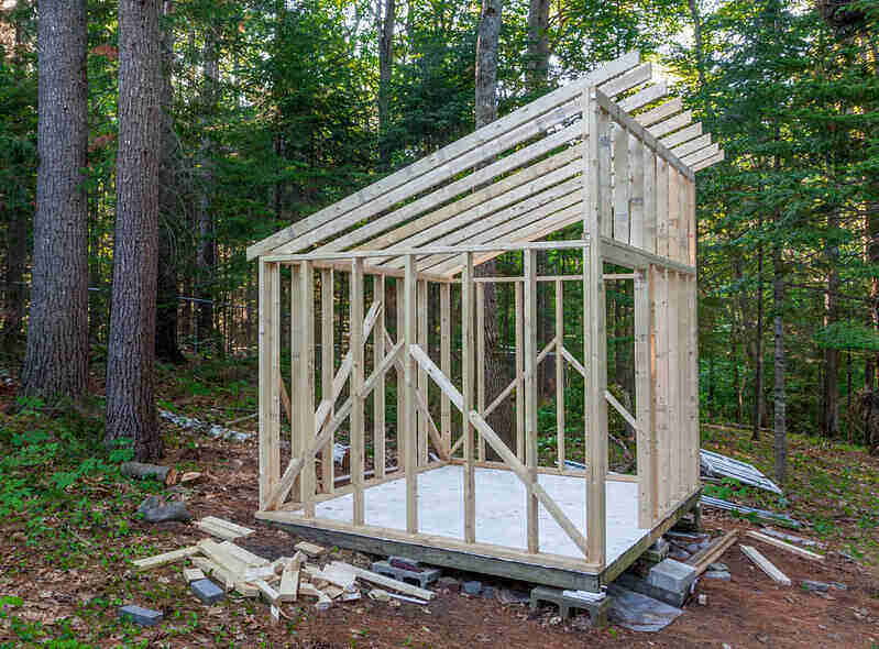 Wooden shed in the process of being built, with only the floor and the framing done